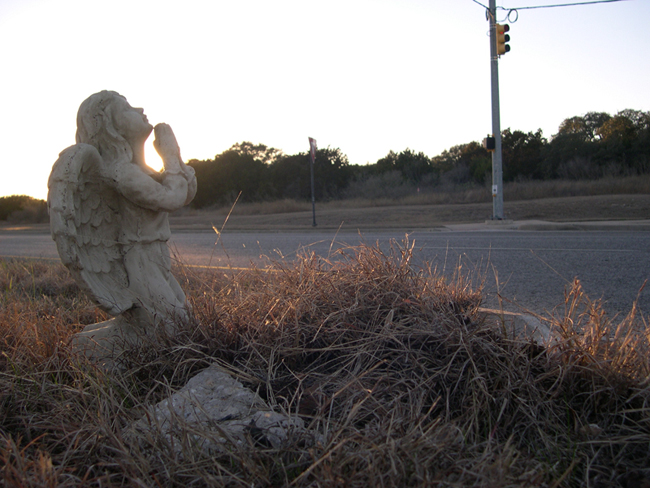 The setting sun glorifies the angel in a side view of the scene.  A piece of broken curb is nestled in the grass.