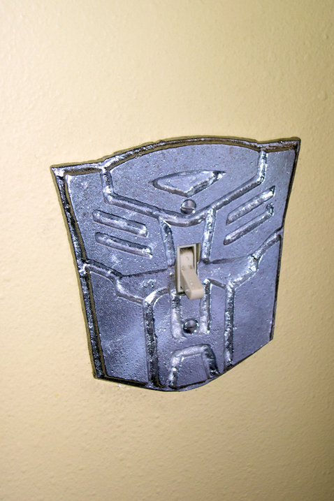 Autobot symbol in quarter-inch sandcast plate aluminum with raised details and appropriate piercings installed over a lightswitch.