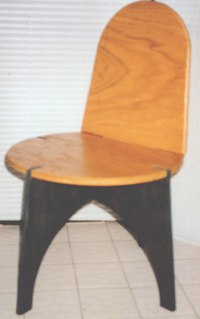 The chair back is secured to the axial leg-piece, through the seat, by a wide tab on its bottom edge. The back secures the seat in place, and is in turn held fast by gravity and friction.