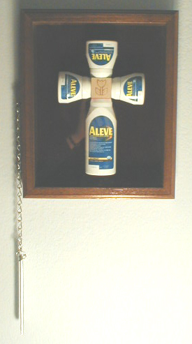 The cross is formed from 4 OTC pain-pill bottles in 3 different sizes, secured by screws through lids into central wooden play-block, with pyrographed flower icon prominent.  Cross is secured in glass-fronted wooden display case lined with burgandy velvet and equipped with external chain and breaker bar, like a fire extinguisher cabinet.