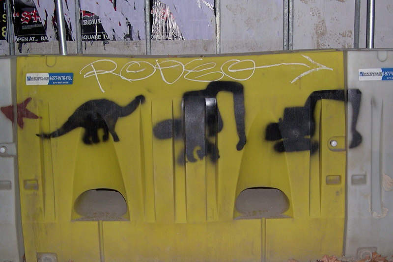 3 spraypainted black glyphs on a yellow barrier morph from a brontosaur to an excavator.