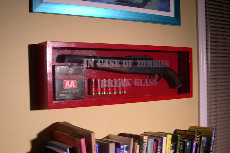OSHA-red box mounted on wall, with glass faceplate bearing etched words IN CASE OF ZOMBIES BREAK GLASS.  Within are a shotgun, some loose shells, and a box of ammo.