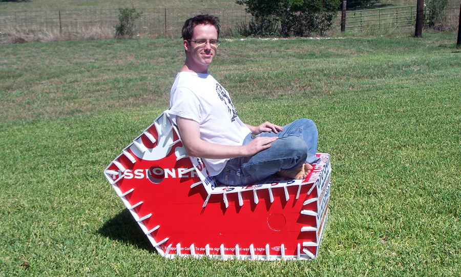 Myself seated in street spam lounger prototype, showing profile against grassy hill.