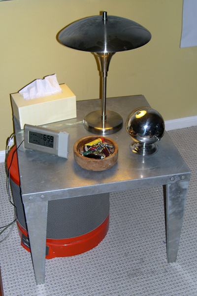 A galvanized sheet metal water heater stand serving as bedside table, with matching stainless steel lamp.
